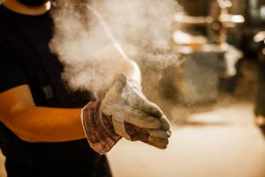 warehouse worker cleaning dust from his gloves