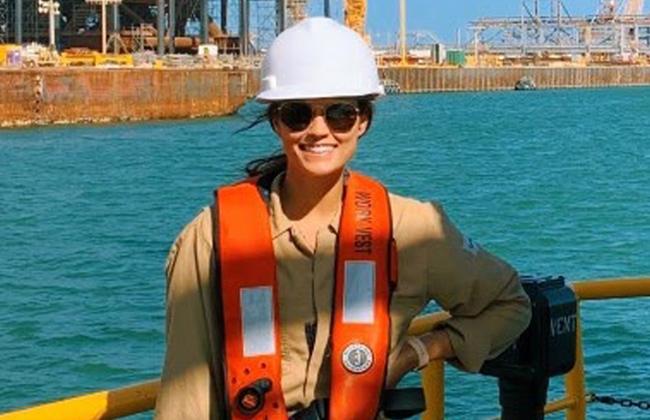Grace wearing hard hat and orange vest